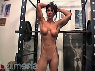 In this SheMuscle® gym video, a hottie is bodybuilding, doing squats,...