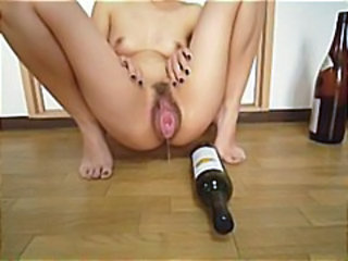 Japanese girl is using a champagne bottle in her big pussy