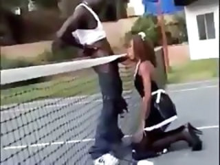 Ebony maid drops to her knees on the tennis court to suck cock