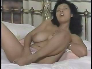 Big-boobed brunette does a slow striptease and touches herself