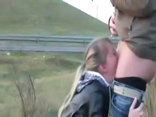 Blonde is on her knees sucking his cock on the side of the road