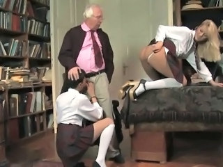 Two girls suck on an old cock