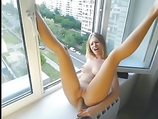 Cam girl masturbates with a dildo near her window.