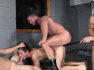 Rough muscled guards drilling prisoner